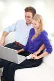Happy young couple using laptop in living room Stock Image