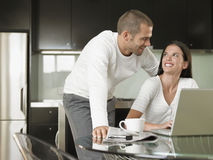Happy Young Couple Using Laptop. Happy Young couple looking at each other while using laptop in modern kitchen Royalty Free Stock Images