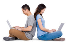 Happy young couple using laptop while sitting back to back Royalty Free Stock Photography