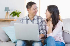 Happy young couple using laptop Stock Photo