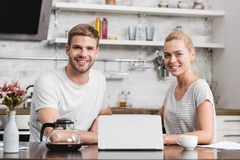 happy young couple using laptop and smiling at camera stock photo