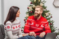 Couple using laptop at christmastime. Happy young couple using laptop and smiling each other at christmastime royalty free stock photography