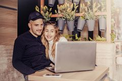 Happy young couple is using a laptop  at the cafe Royalty Free Stock Image