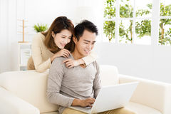 Happy young couple using laptop on sofa Royalty Free Stock Images