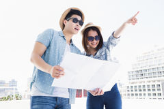 Happy young couple using map for direction Royalty Free Stock Photography