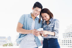 Happy young couple using mobile phone Stock Image