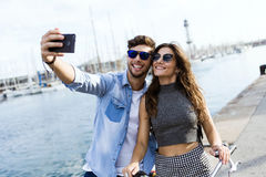 Happy young couple using mobile phone in the street. Royalty Free Stock Photos