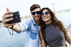 Happy young couple using mobile phone in the street. Stock Photo