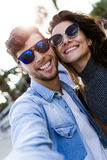 Happy young couple using mobile phone in the street. Stock Image