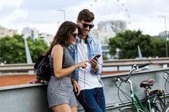 Happy young couple using mobile phone in the street. Royalty Free Stock Images