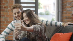 Happy young couple using smartphone at home. Attractive young couple making selfies with smart phone while sitting on a couch in a living room in modern loft stock footage