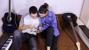 Happy Young Couple using Tablet PC on the couch. Young happy boy and girl at home, lying on a folding couch and brown look at a tablet computer, smiling and stock video footage