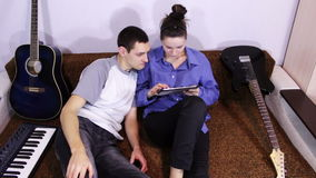 Happy Young Couple using Tablet PC on the couch stock footage