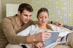 Happy young couple using tablet PC at home Stock Photos