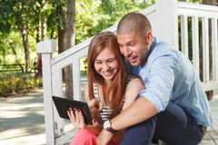 Happy young couple using a tablet PC in the park Stock Photos