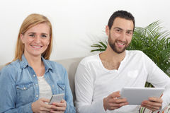 Happy young couple using  tablet and phone Stock Photography