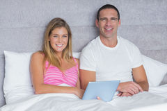 Happy young couple using their tablet pc together in bed Royalty Free Stock Photos