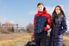 Happy young couple on vacation. Standing arm in arm on the railway line with their packed luggage smiling at the camera as they wait for the train Royalty Free Stock Photography