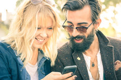 Happy young couple with vintage clothes having fun with phone stock photography