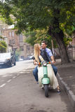 Happy young couple by a vintage scooter on the street Royalty Free Stock Photos