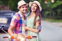 Happy young couple by a vintage scooter in the street wearing ha Stock Photo