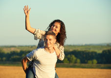 Happy young couple walk on country outdoor, romantic people concept, summer season, girl riding on man back and waving Stock Image