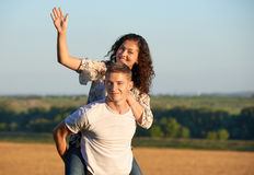 Happy young couple walk on country outdoor, romantic people concept, summer season, girl riding on man back and waving Royalty Free Stock Photos