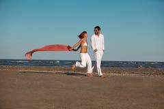 Happy, young couple walking along the seashore Royalty Free Stock Photography