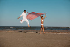 Happy, young couple walking along the seashore Royalty Free Stock Photos