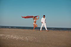 Happy, young couple walking along the seashore Stock Image