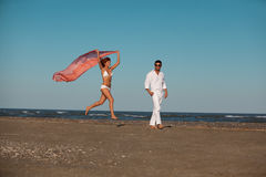 Happy, young couple walking along the seashore Stock Photos