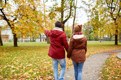 Happy young couple walking in autumn park Royalty Free Stock Photos