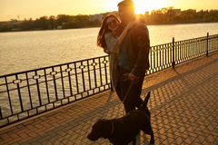 Happy young couple walking with dog on street. Stock Image
