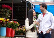 Happy young couple walking by flower shop Stock Image