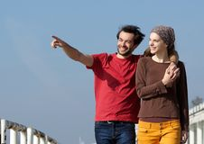 Happy young couple walking outdoors and pointing Royalty Free Stock Image
