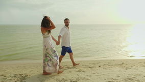 Happy young couple walking in the rain. It goes along the shore along the sea. Great rest together stock video footage