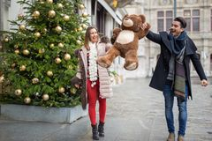 Happy young couple walking on a street at chrstmas time holding royalty free stock photography