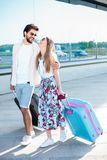 Young couple walking in front of an airport terminal building. Beautiful young couple walking in front of an airport terminal building, pulling suitcases and royalty free stock photography