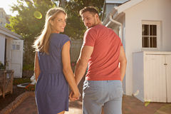 Happy young couple walking to their house. Shot of young couple in backyard on a bright sunny day. They are walking to their house hand in hand, looking over royalty free stock photography