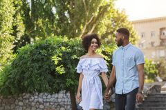 Happy young couple walking together in park royalty free stock photography
