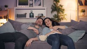 Happy young couple watching funny show on TV laughing eating popcorn at home. Lying on sofa together late at night. People, fun and mass media concept stock footage