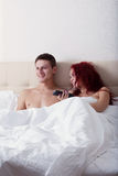 Happy young couple watching TV while lying in bed Stock Images