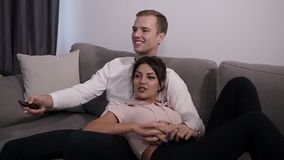 Happy young couple watching tv and talking at home sitting in a comfortable couch in the livingroom at home. Young woman stock video footage