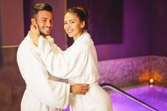 Happy young couple wearing bathrobe enjoying the spa day during their honeymoon - Romantic lovers having relax in a hotel spa royalty free stock photos