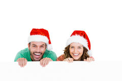 Happy young couple wearing santa hat. Portrait of happy young couple wearing santa hat on white background Stock Image