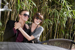 Happy young couple wearing sunglasses on patio. Happy young romantic couple wearing sunglasses on patio Stock Photography