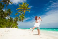 Happy young couple in white clothes having fun by the beach stock image