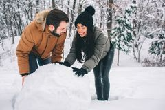 Happy Young Couple in Winter . Family Outdoors. man and woman looking upwards and laughing. Love, fun, season and people stock photography
