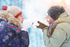 Happy Young Couple in Winter Park blowing snow. laughing and having fun. Family Outdoors. Royalty Free Stock Photography