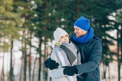 Happy Young Couple in Winter Park laughing and having fun. Family Outdoors. Royalty Free Stock Image